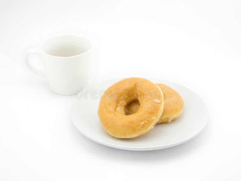 Munk och kopp kaffe på vit bakgrund royaltyfria bilder