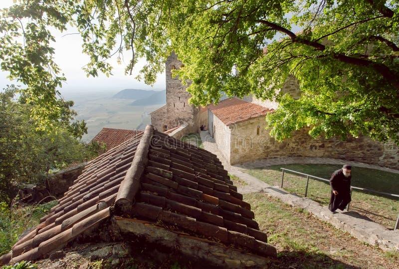 Munk som går förbi gamla byggnader av den ortodoxa kloster i den Alazani dalen royaltyfria bilder