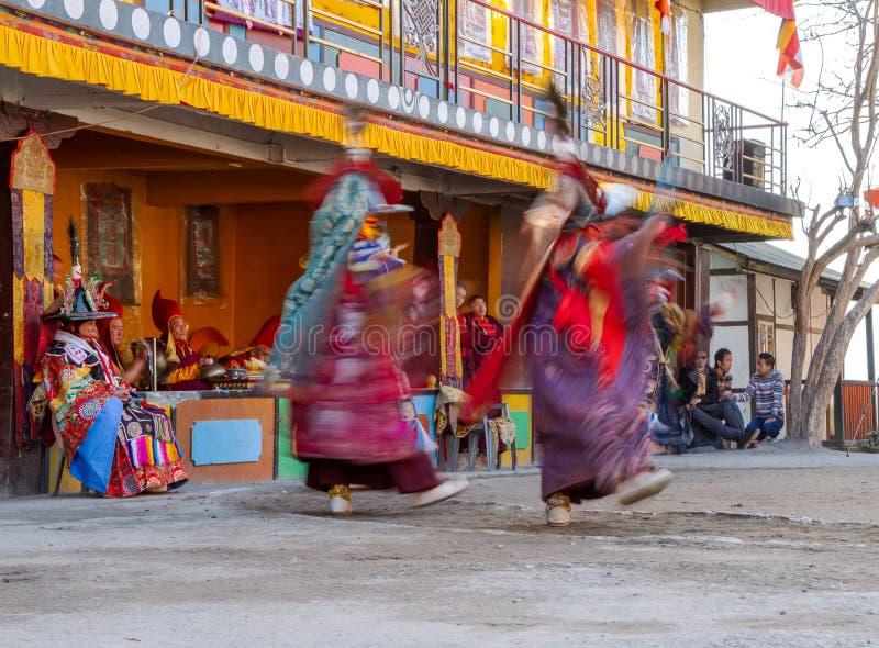 Munkar utför maskerad och kostymerad dans av tibetan buddism under Chamdansfestivalen Dansare gjorde suddig rörelse arkivbilder