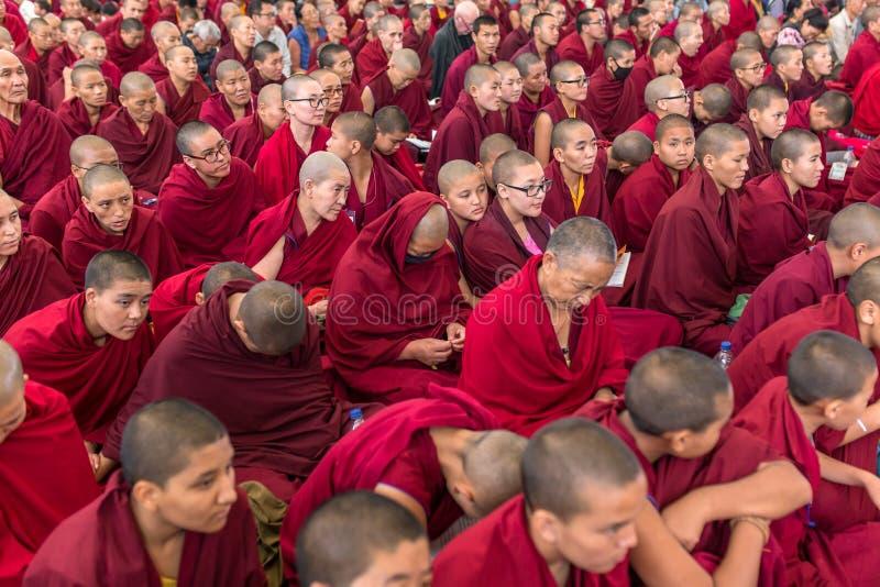 Munkarna och det tibetana folket som lyssnar till hans helighet 14na Dalai Lama Tenzin Gyatso som ger undervisningar i hans uppeh royaltyfria bilder
