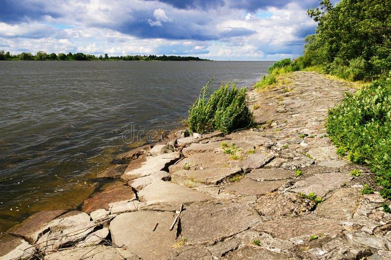 Munnen av Vistulaet River till Östersjön med en stenflodinvallning på en solig dag arkivbild