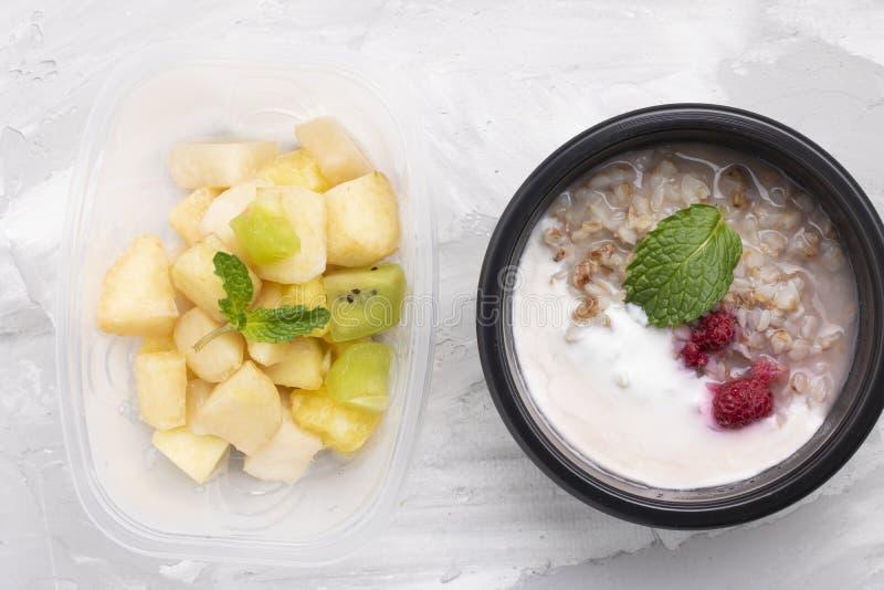Muntblad met Appelen en ananassenplakken met oatmeals en kwark met bessen, voedselcontainers stock foto