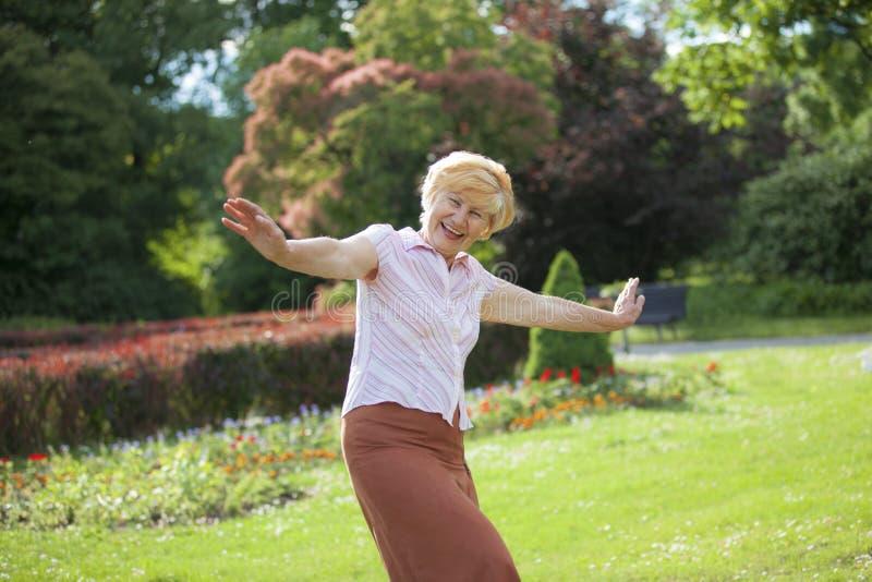 Munterhet. Förtjust skämtsam mogen kvinna med utsträckta armar som utanför skrattar arkivbilder