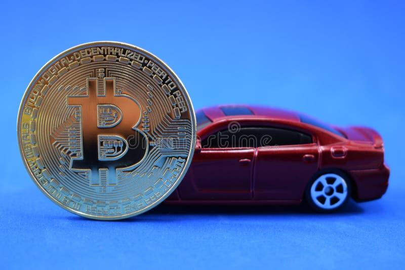Muntstuk bitcoin en rode auto op een blauwe achtergrond, een symbool van rijkdom en succes royalty-vrije stock fotografie