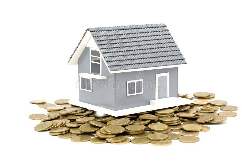 Muntstuk en Grijs huismodel dat op witte achtergrond, Onroerende goedereninvestering wordt geïsoleerd royalty-vrije stock afbeelding