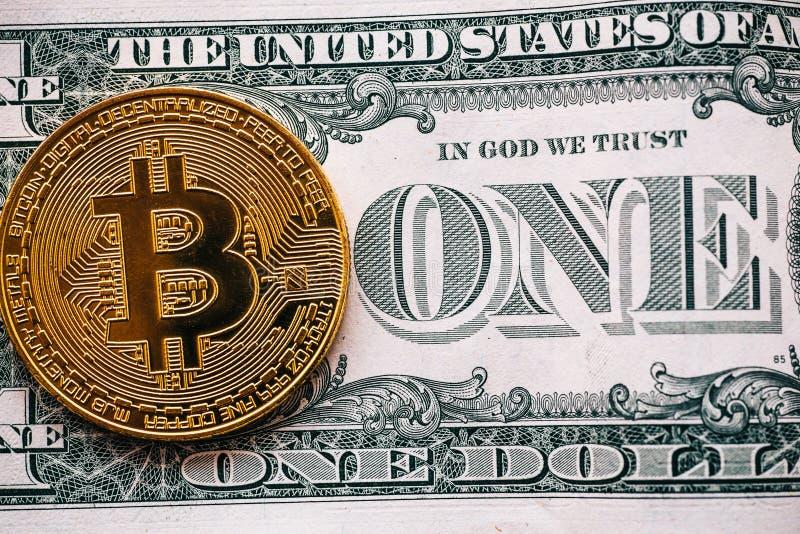 Muntstuk van Cryptocurrency het gouden bitcoin op één dollarbankbiljet - symbool van virtueel geld en oud papiergeld stock afbeelding