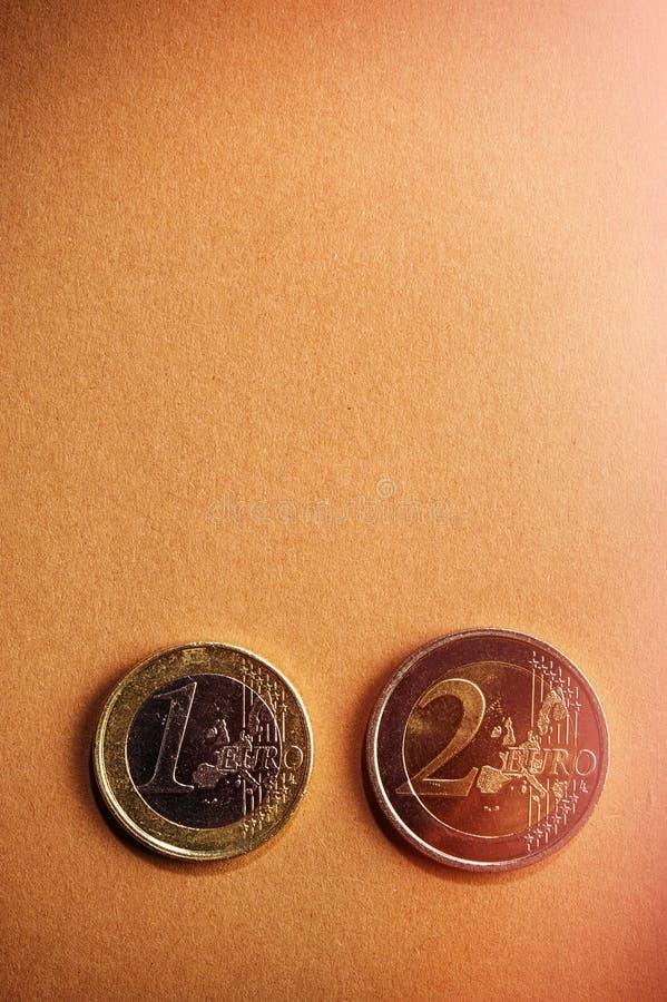 Muntstukken één en twee euro op een achtergrond van karton royalty-vrije stock foto