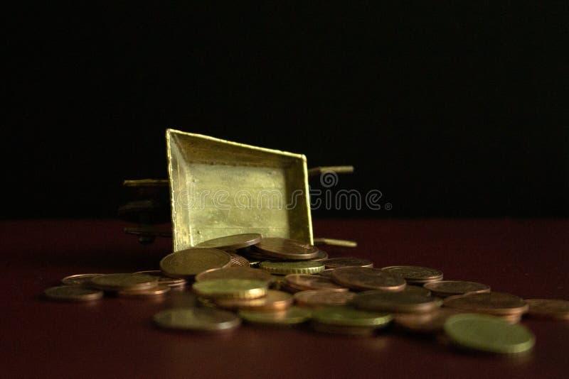 Muntstukken die van een gouden uitstekende kruiwagen op donkere achtergrond vallen royalty-vrije stock afbeeldingen