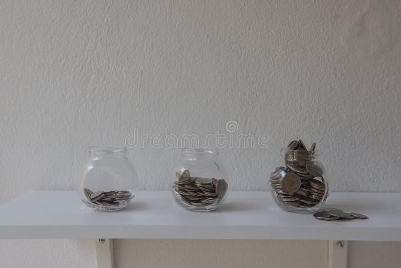 Muntstukken in een glaskruik, het Geldstap van de conceptenbesparing met stortingsmuntstuk in de groeiende zaken van de bankstape stock fotografie
