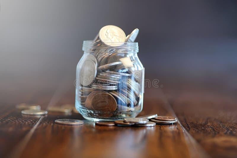 Muntstukken in een glaskruik op een houten vloer Zakbesparingen van muntstuk royalty-vrije stock afbeeldingen