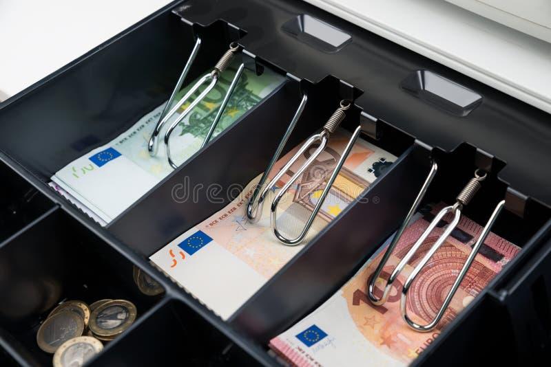 Muntstukken en Bankbiljet in Kasregister stock afbeelding