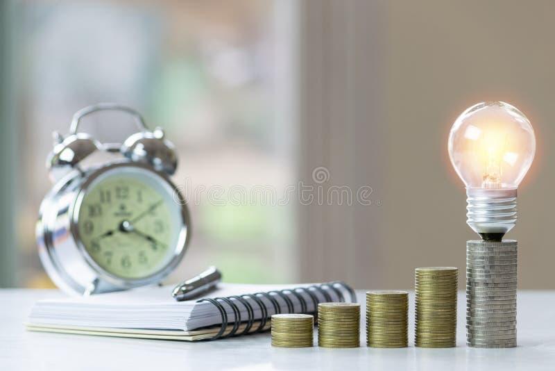 Muntstukken met gloeilamp, klok en notitieboekje op lijst voor zaken, financiën, sparen concept royalty-vrije stock afbeelding