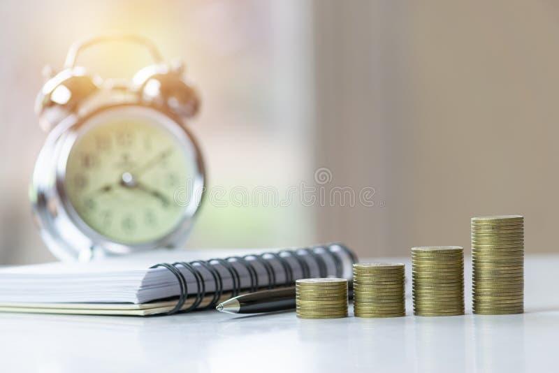 Muntstukken met klok en notitieboekje op lijst voor zaken, financiën, sparen concept royalty-vrije stock afbeeldingen