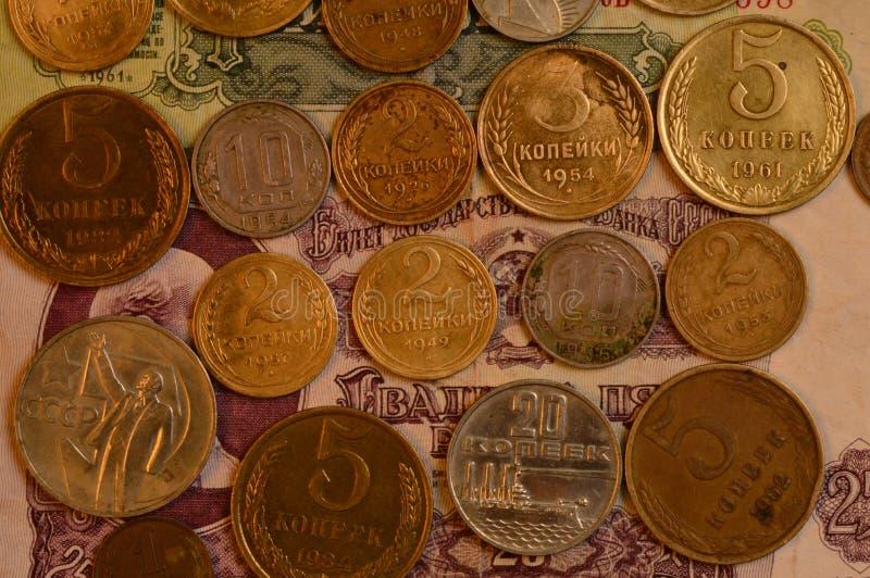 Muntstukken Sovjetcopeck vanaf 1926 tot 1988 tegen de achtergrond van document roebels van die jaren stock foto
