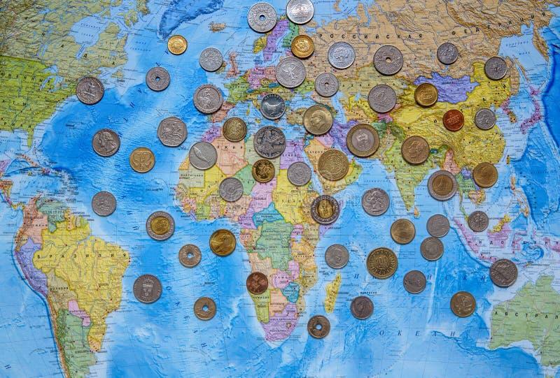 Muntstukken van verschillende landen op de achtergrond van de wereldkaart royalty-vrije stock afbeelding
