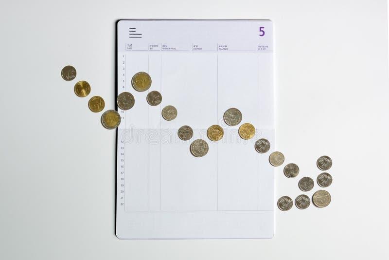 Muntstukkenserie om grafiek te tonen die op de rekeningsboek van de bankbesparing dalen stock fotografie