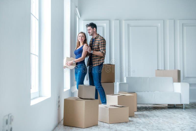 Muovendosi, riparazioni, nuova vita La coppia nell'amore gode di nuovo appartamento fotografia stock libera da diritti