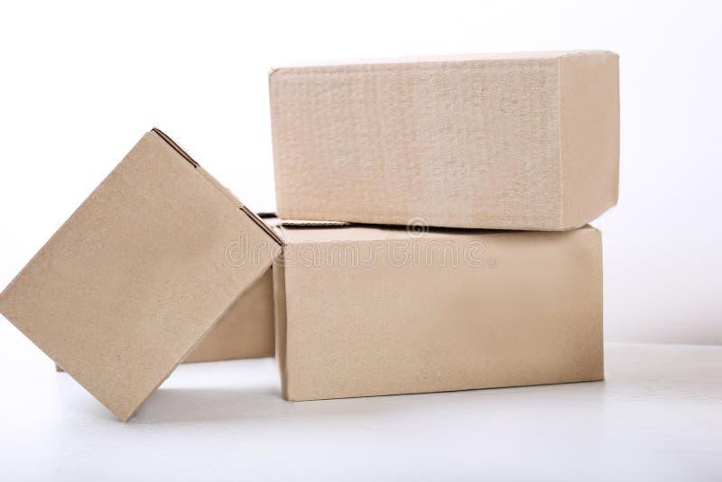 Muoversi dentro Pila di scatole di cartone su fondo bianco Fine in su fotografie stock libere da diritti