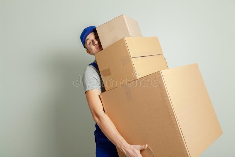 Muoversi di giorno Consegna delle merci da acquisto nel deposito online Il caricatore o il corriere porta le scatole di cartone p fotografia stock libera da diritti