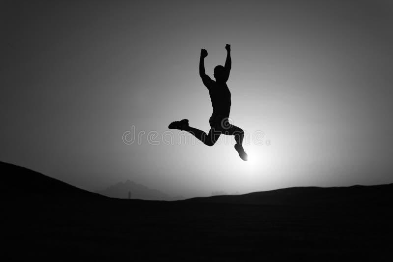 Muoversi Keep Salto di moto dell'uomo della siluetta davanti al fondo del cielo di tramonto Motivazione quotidiana Stile di vita  immagini stock libere da diritti