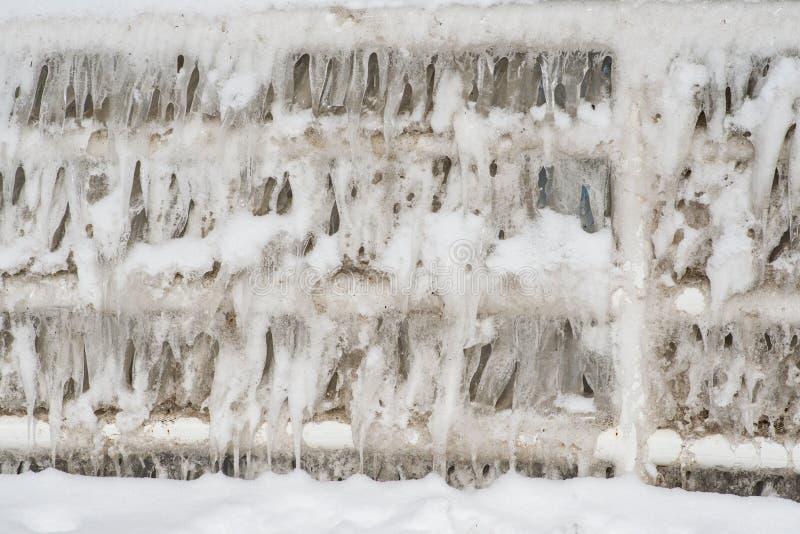 Mur épais des glaçons couvrant la barrière de sécurité un hiver ensoleillé photos stock