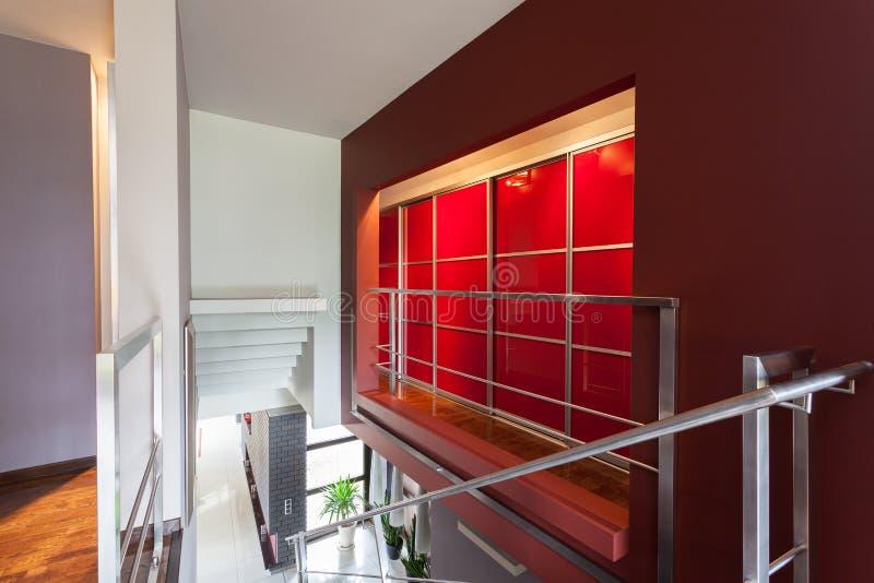 Mur allumé par rouge dans la maison moderne image stock