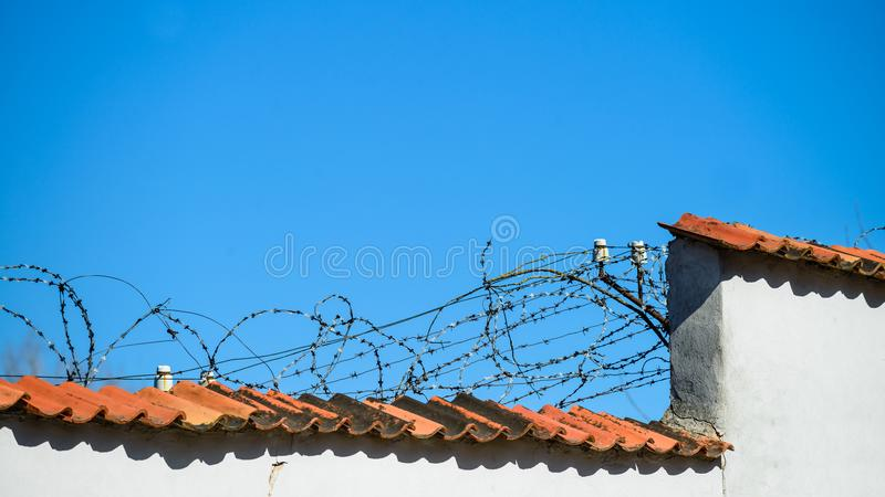 Mur avec la barrière de barbelé au jour ensoleillé Symbole d'emprisonnement photos libres de droits