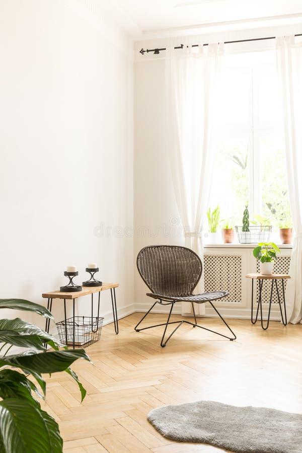 Mur blanc de fond avec l'espace vide dans un intérieur à haut plafond de pièce avec une chaise de rotin et en métal dans les tabl photos stock