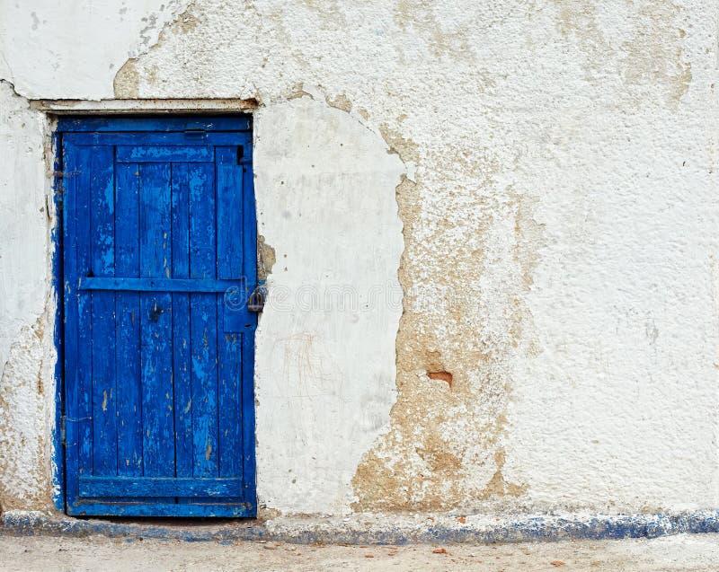 Mur blanc de vieille maison avec la trappe bleue images stock