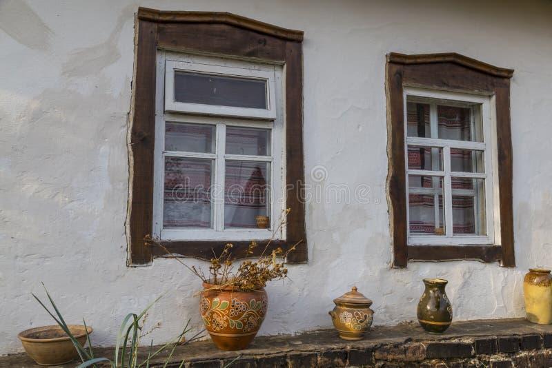 Mur blanc de vieille maison d'argile avec deux fenêtres avec le cadre en bois photos libres de droits
