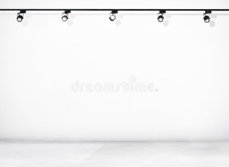 Mur blanc et plancher en béton avec des projecteurs photo libre de droits