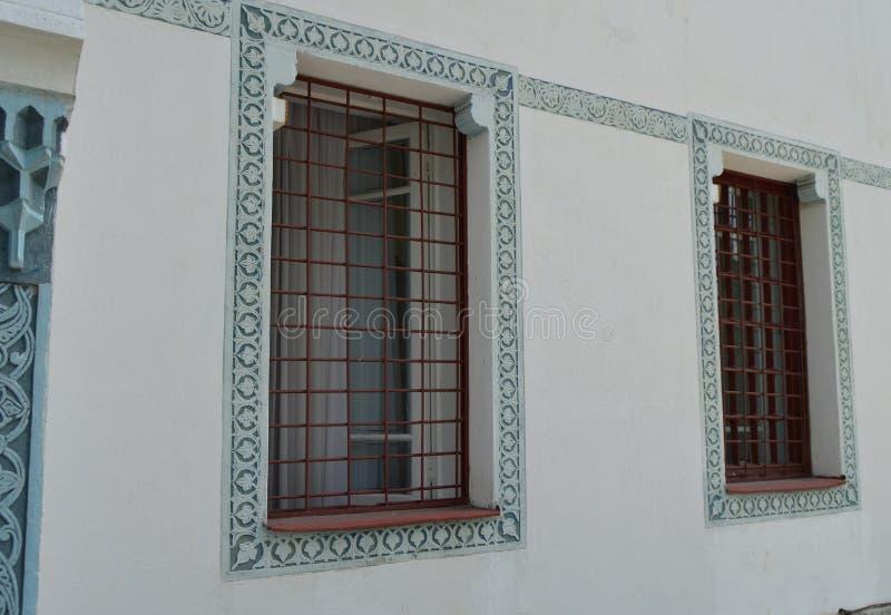 Mur blanc, fenêtre avec des barres et ornement oriental bleu, style arabe traditionnel images libres de droits