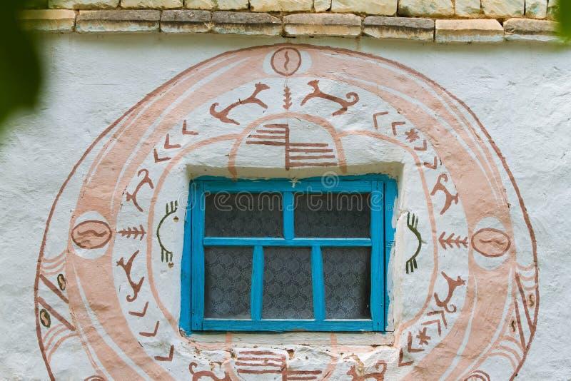 Mur d'une ancienne maison de campagne soviétique avec des peintures symboliques de style Trypillya autour de la fenêtre photographie stock libre de droits