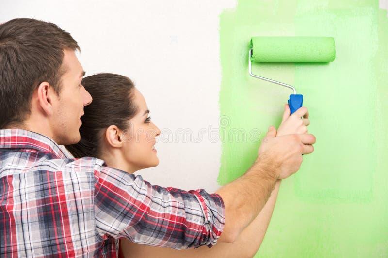 Mur de aide de peinture de femme d'homme image stock