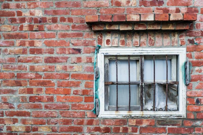 Mur de briques âgé et fenêtre très vieille avec le gril en acier photo libre de droits