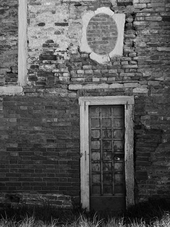 Mur de briques antique avec les fenêtres et la porte bloquées photos libres de droits