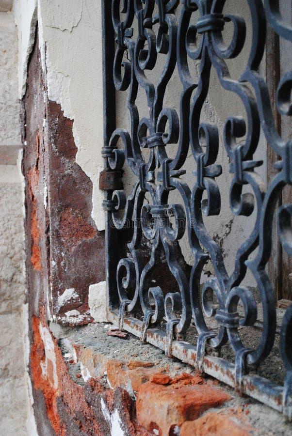 Mur de briques avec la fenêtre antique de fer photos stock