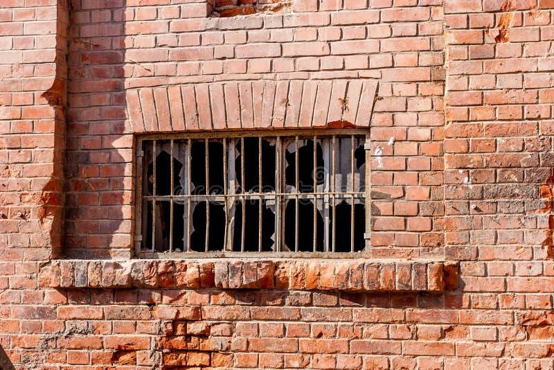 Mur de briques avec la fenêtre et le verre cassé image libre de droits