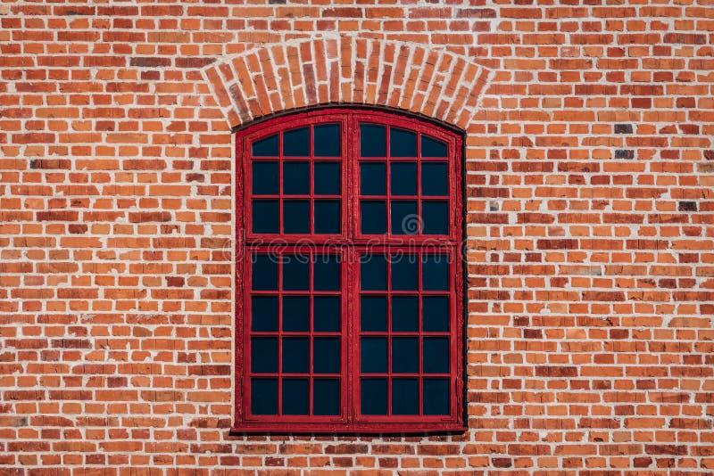 Mur de briques avec la fenêtre rouge photo stock