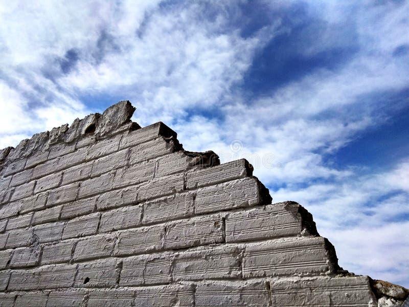 Mur de briques blanc dans le ciel photographie stock