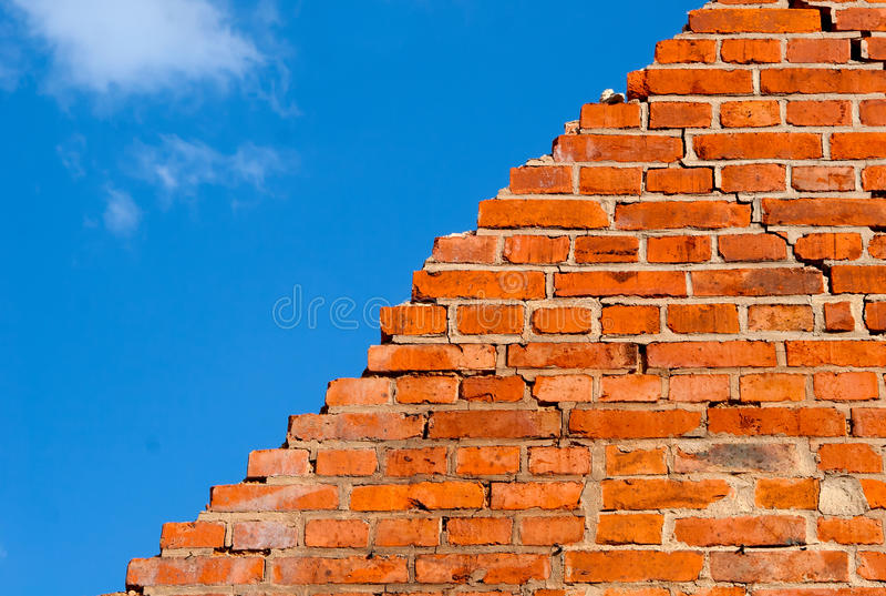 Mur de briques cassé contre le ciel photographie stock libre de droits