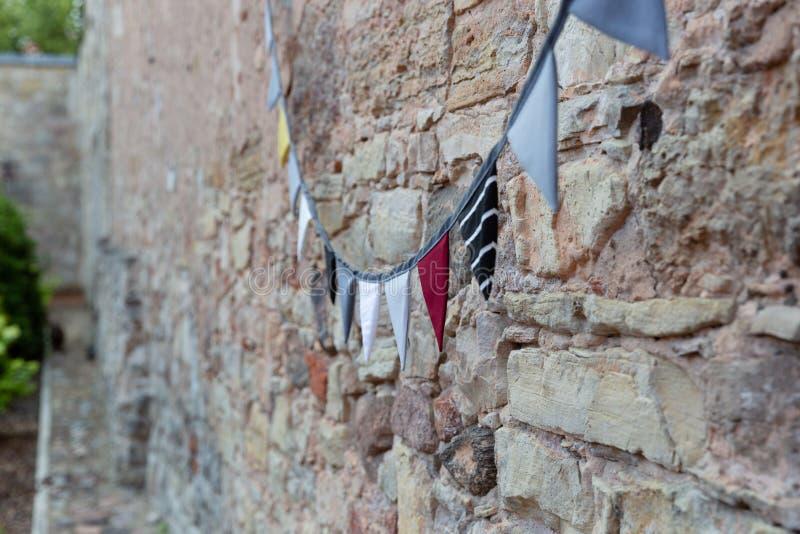 Mur de briques de construction extérieur décoré des drapeaux de pair de tissu de cru Festival, concept de célébration photos stock
