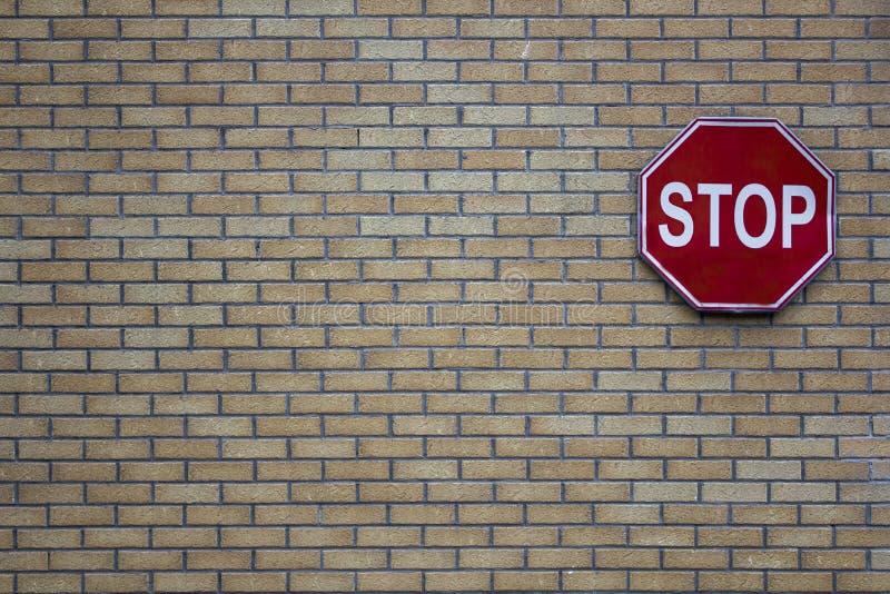 Mur de briques des briques grises et jaunes avec un signe rouge d'arrêt de route Texture de surface approximative photos libres de droits