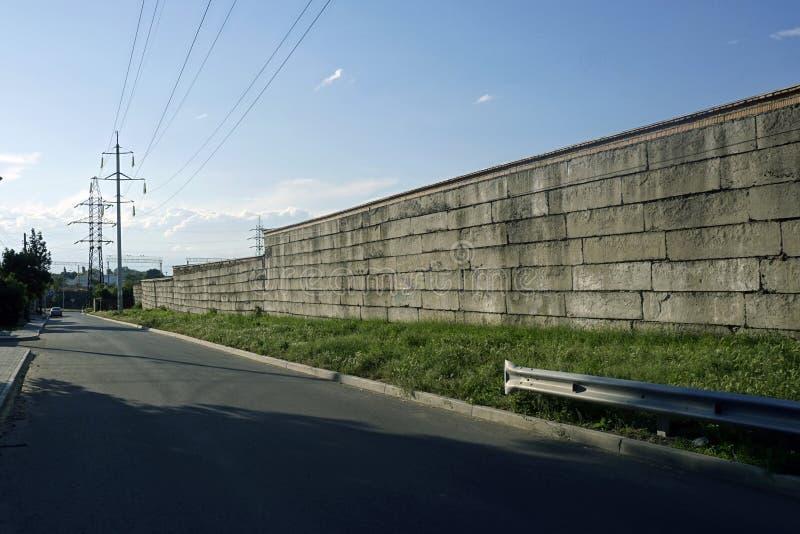 Mur de briques en bas de la rue avec l'électricité et le ciel bleu image libre de droits