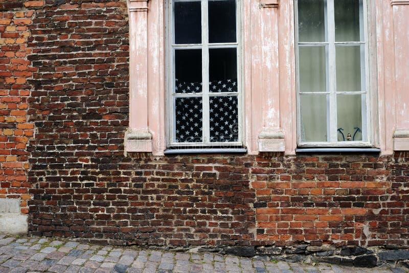 Mur de briques et drapeau américain dans la fenêtre photos stock