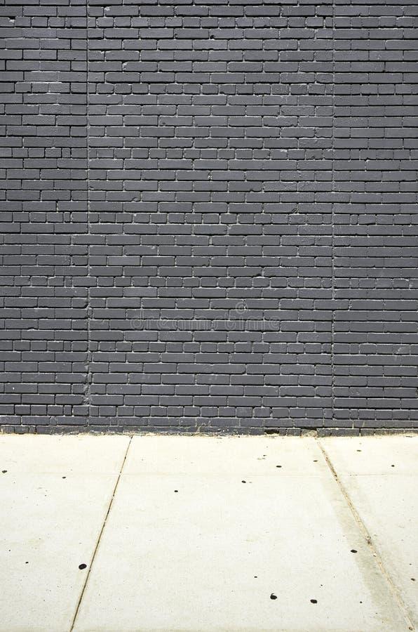 Mur de briques et plancher noirs de concret photographie stock