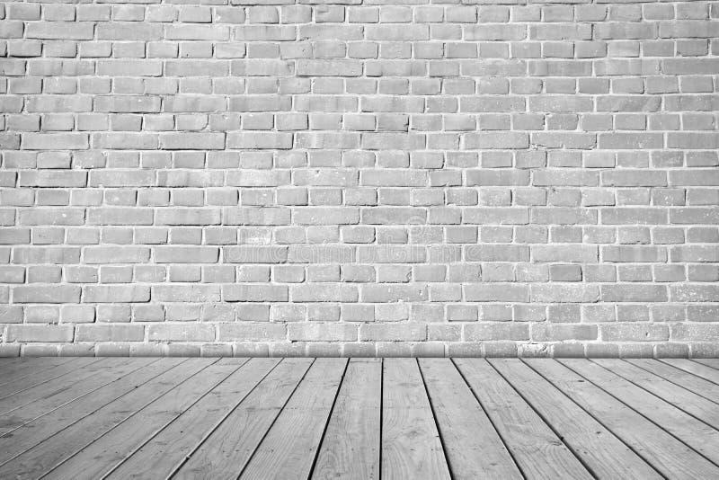 Mur de briques gris sur le plancher en bois image stock Mur de brique gris