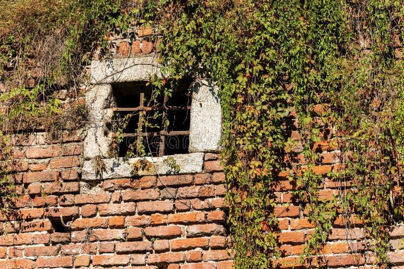 Mur de briques médiéval - fenêtre avec des barres de fer travaillé photographie stock