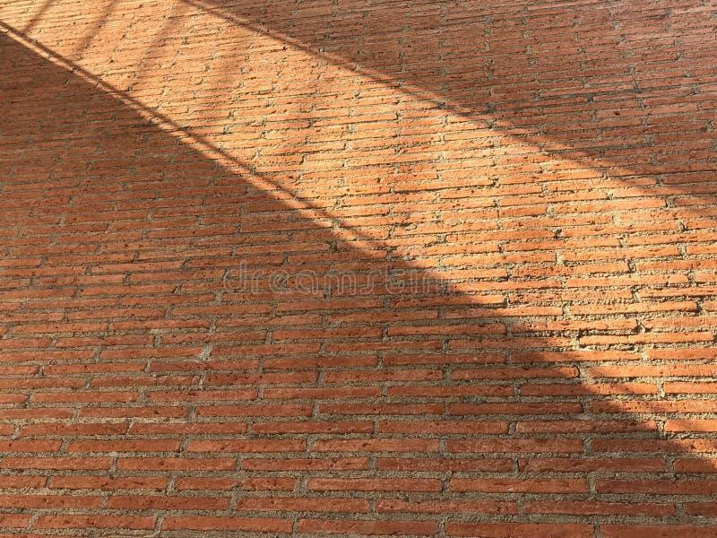 Mur de briques rouge avec les croix légères d'ombre là-dessus dans la forme diagonale photographie stock libre de droits