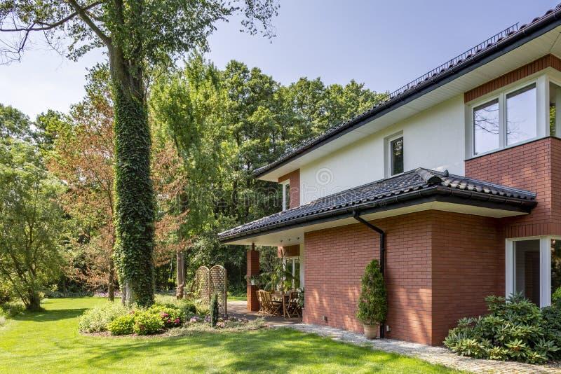 Mur de briques rouge de maison avec le toit et les fenêtres photos libres de droits